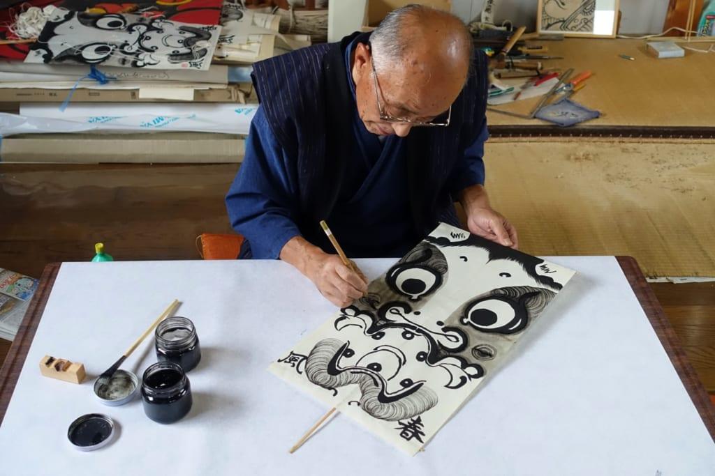 M. Ono, dessinant avec soin le motif de son cerf-volant à l'encre noire