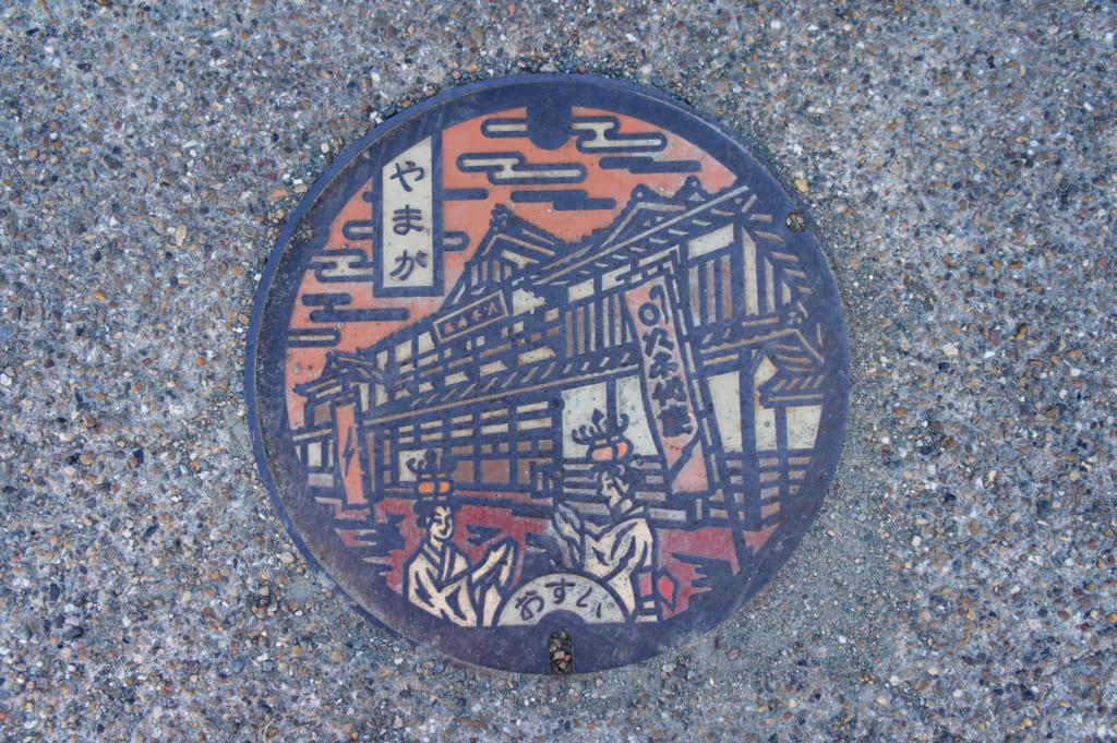 Plaque d'égout représentant le théâtre Yachiyo-za de Yamaga et deux danseuses portant des lanternes sur la tête