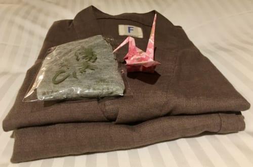 Pyjama plié, disposé sur le lit avec une grue en origami