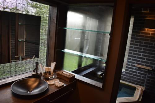 L'espace salle de bain, aux matières nobles et sombres, éclairé par grandes fenêtres