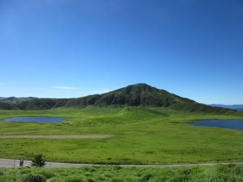 Les plaines de la caldera du mont Aso sous un ciel bleu sans nuages