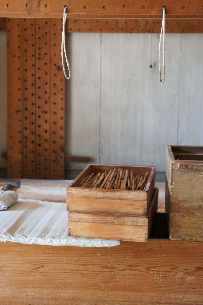 Ustensiles en bambou rangés dans des caisses en bois dans la fabrique de somen Saruwatari