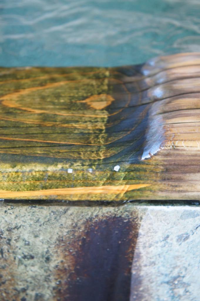 Détail de l'onsen privatif : eau coulant sur le rebord de bois