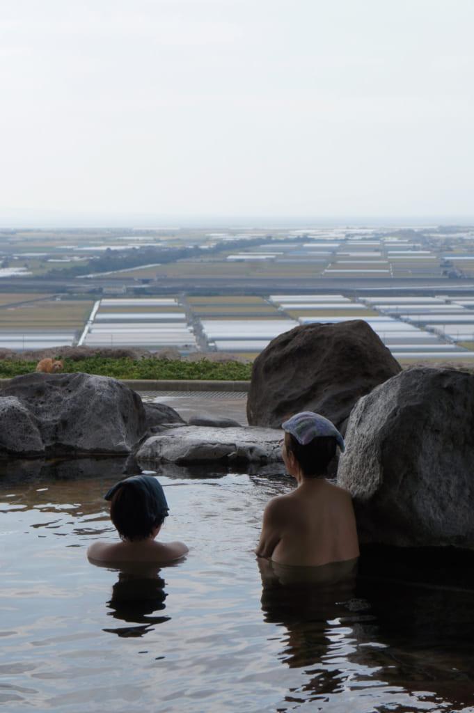 Deux femmes prenant un bain en profitant de la vue au Kusamakura onsen Tensui