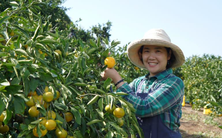 Mme Mizumoto, posant près d'un arbre aux branches chargées de fruits