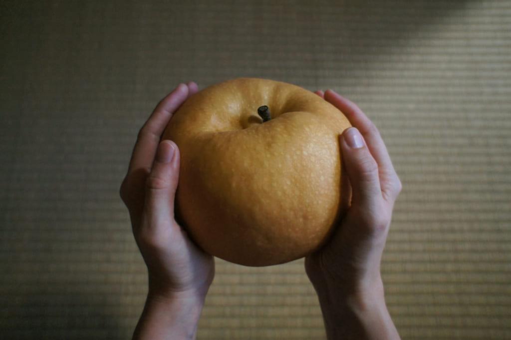 Un Jumbo nashi d'Arao, tenu par deux mains
