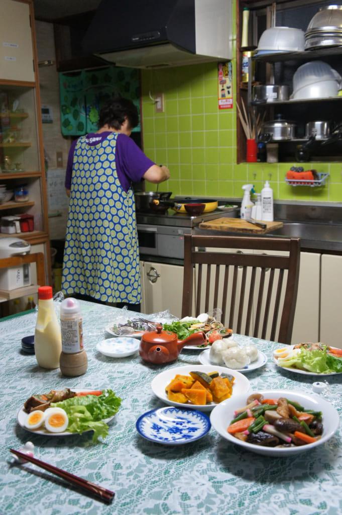 Mme Yonemura en cuisine, derrière la table servie