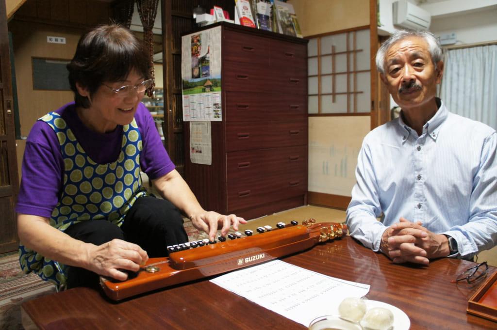 Le couple Yonemura dans leur salon, Keiko joue du taishogoto