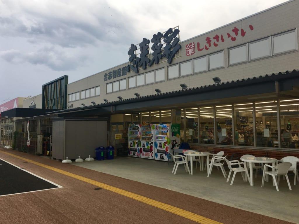 Façade du magasin Shikisaisai, devant lequel sont disposés tables et chaises