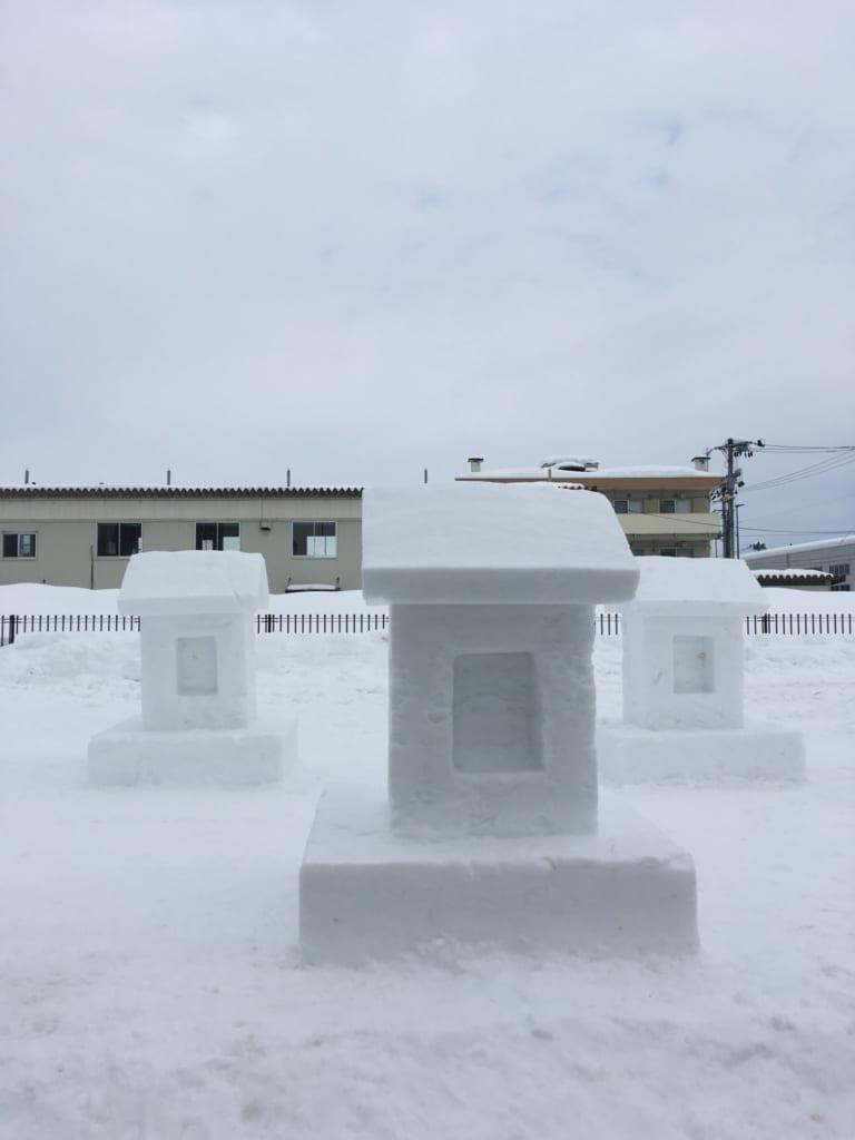 Sculptures de temples et chiens dans la neige durant le festival Inukko Matsuri