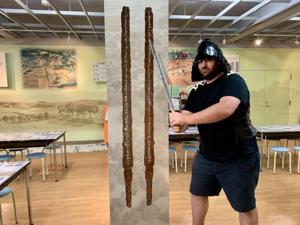 Dave Bret posant près de l'épée retrouvée dans le kofun Irayama