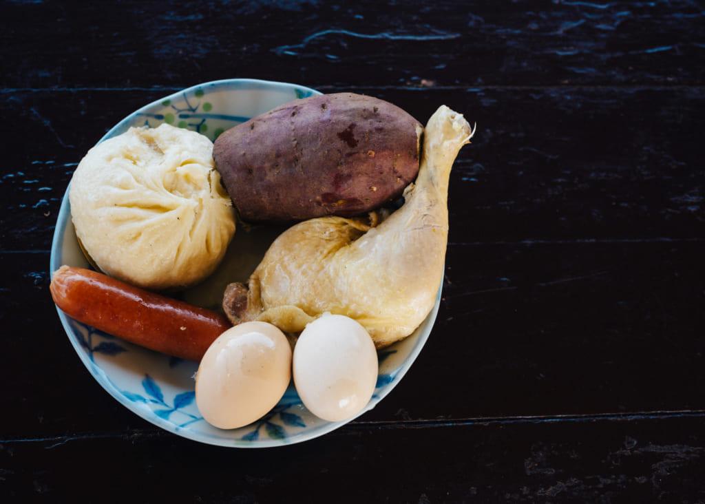 Repas cuis à la vapeur de l'onsen : poulet, patate douce, brioche au porc, saucisse et œufs