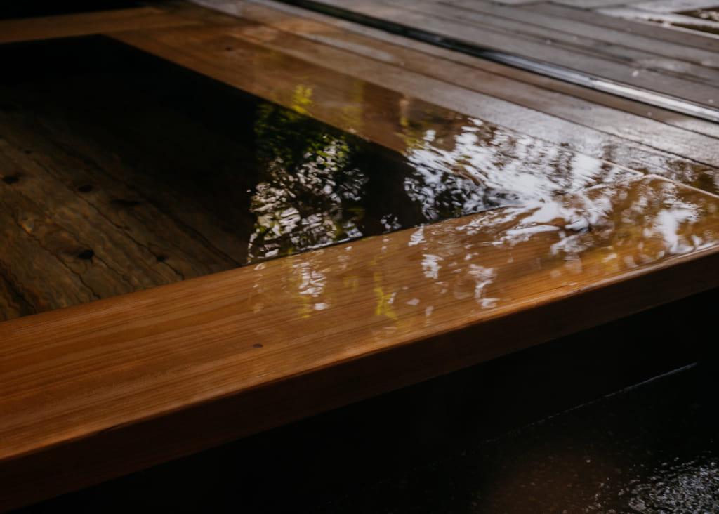 Eau de l'onsen, recouvrant les bords du bassin et reflétant les arbres