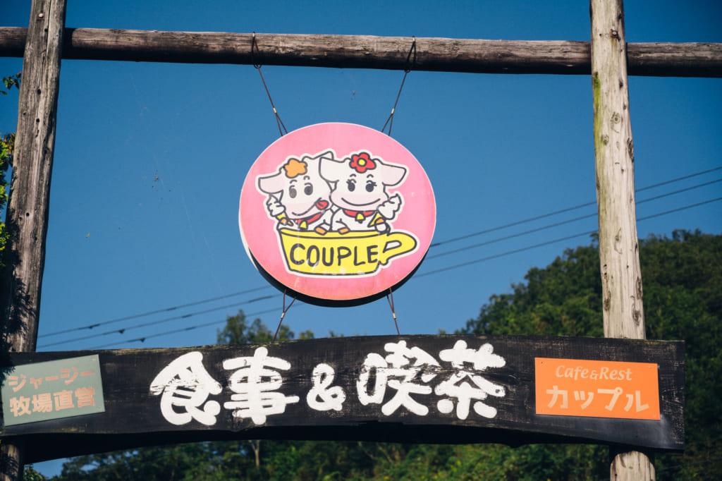 L'enseigne de Couple : deux adorables vaches dessinées sur un fond rose