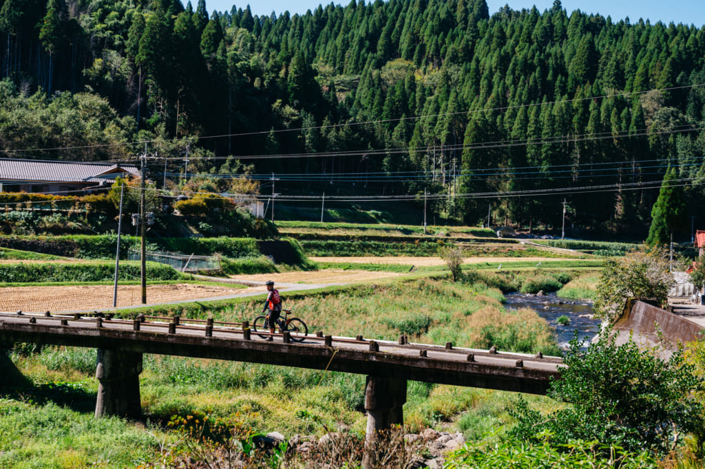 Guide à vélo traversant un petit pont dans la campagne à Kumamoto