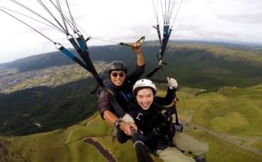 Mika et son instructeur, volant en parapente au-dessus du mont Aso une des activités de plein air à pratiquer à Kumamoto
