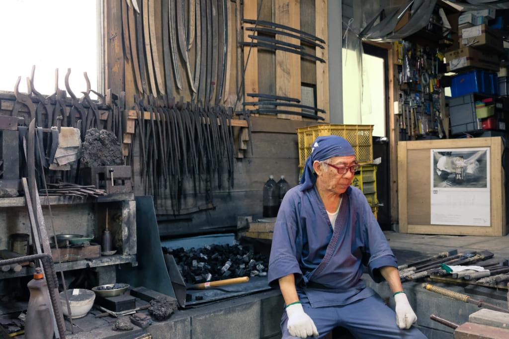 M. Matsunaga et ses nombreuses lames de katana en cours de confection accrochées aux murs de son atelier à Kyushu