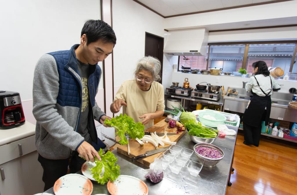 Les personnel de l'auberge apprend à Derek comment cuisiner le petit déjeuner