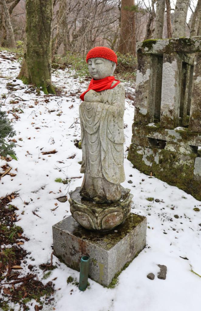 statuette japonaise vêtue d'un bonnet et d'une écharpe rouges