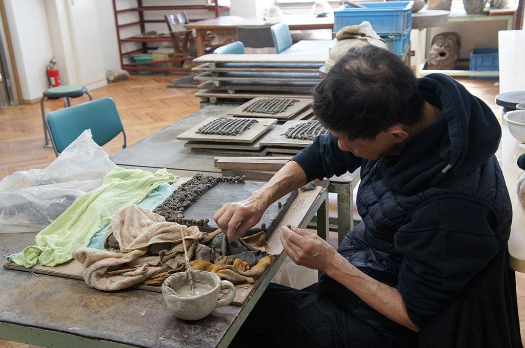 Un pensionnaire en situation de handicap mental travaille à une œuvre en céramique