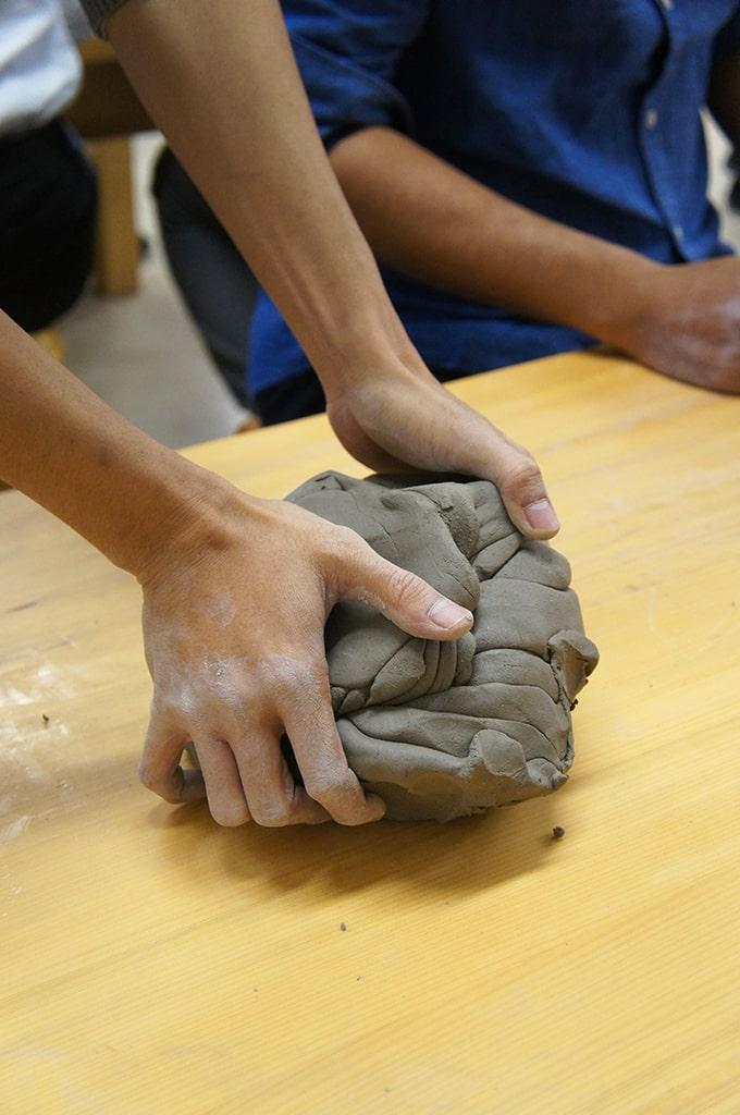 Mains d'une personne pétrissant une boule d'argile