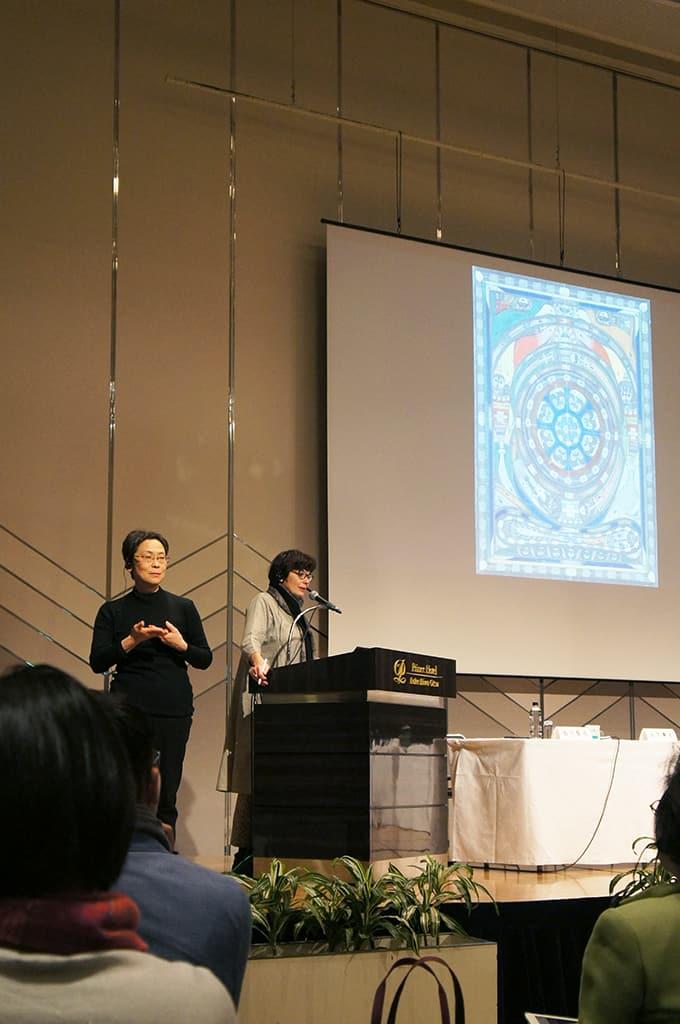 Martine Lusardy, directrice de la Halle Saint Pierre pendant son intervention, traduite en langue des signes par une interprète