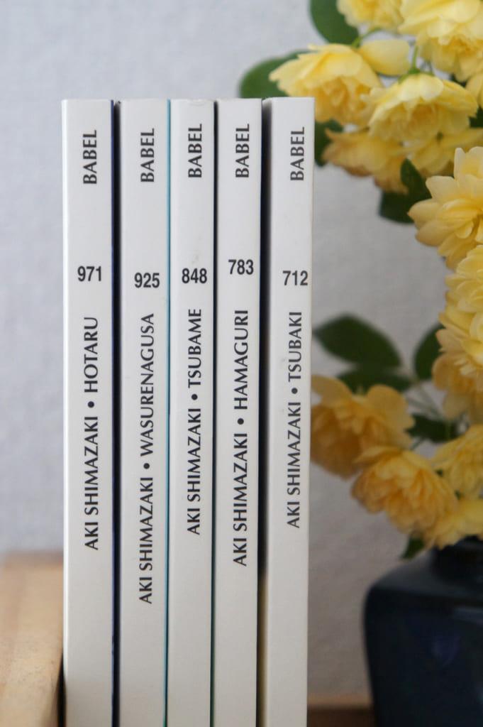 Les livres d'Aki Shimazaki à côté de fleurs jaunes
