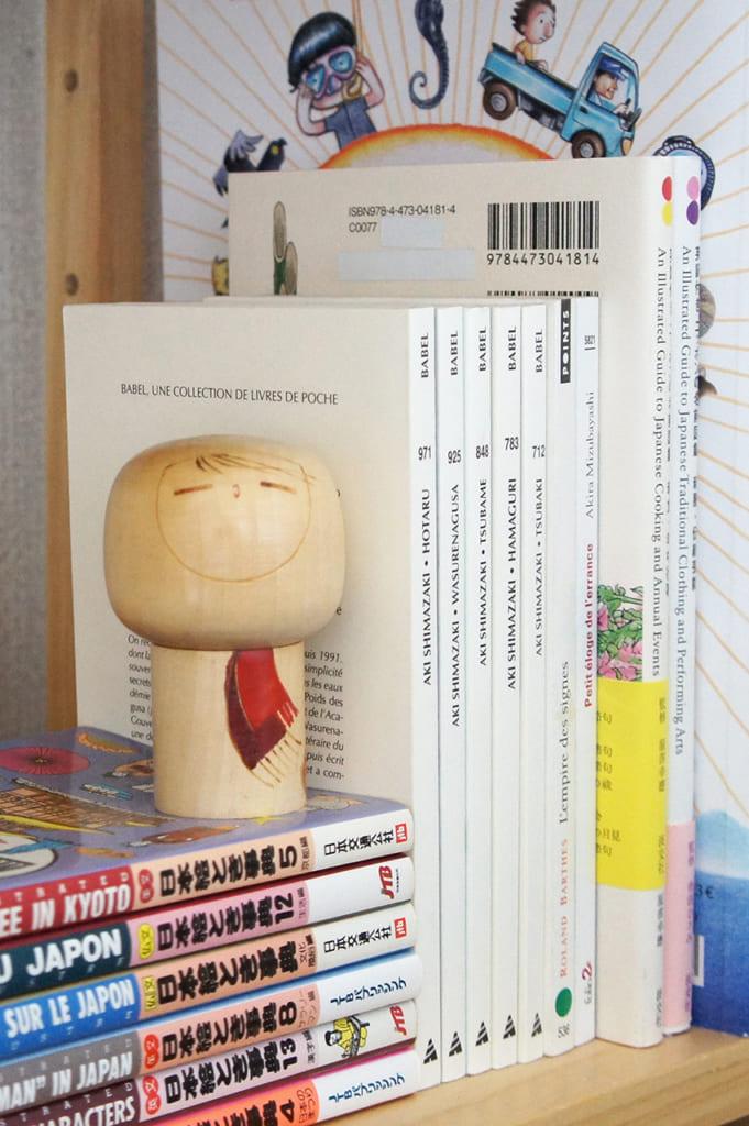 Kokeshi créative avec écharpe devant une sélection de livres sur le Japon