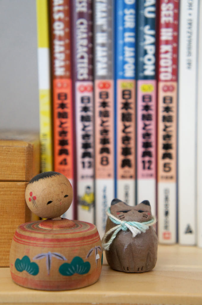 Petite kokeshi et chat en céramique devant des livres