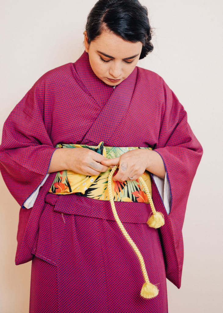 mise en place d'un noeud plat pour maintenir l'obi à l'aide d'un obi-jime