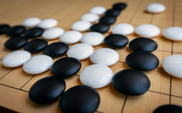 pierres d'un jeu de go posées sur un goban