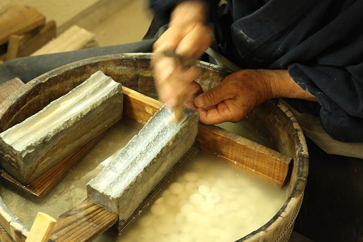 artisan entrain de polir des pierres de go en coquillage