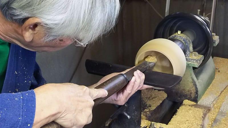 artisan japonais entrain de creser un bol en bois pour un jeu de go