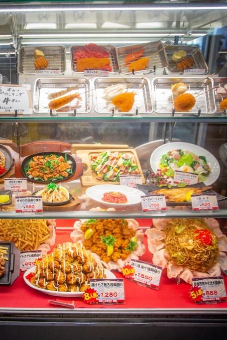 diverses spécialités culinaires dans la vitrine d'un restaurant de shinsekai