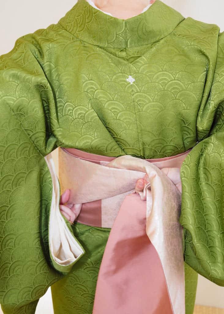 il faut plier le nagoya obi d'une main et s'aider de l'autre main pour arranger le pli