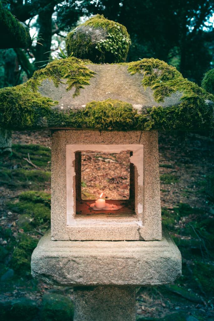 Une bougie allumée dans une lanterne en pierre japonaise