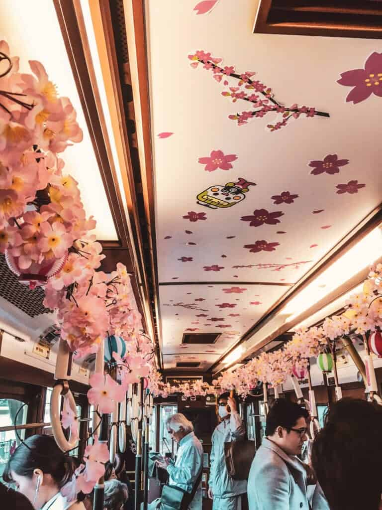 un tramway japonais décoré aux couleurs des cerisiers en fleur