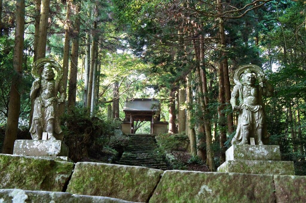 Statues nio de pierre bordant l'escalier devant le temple Futago-ji à Oita