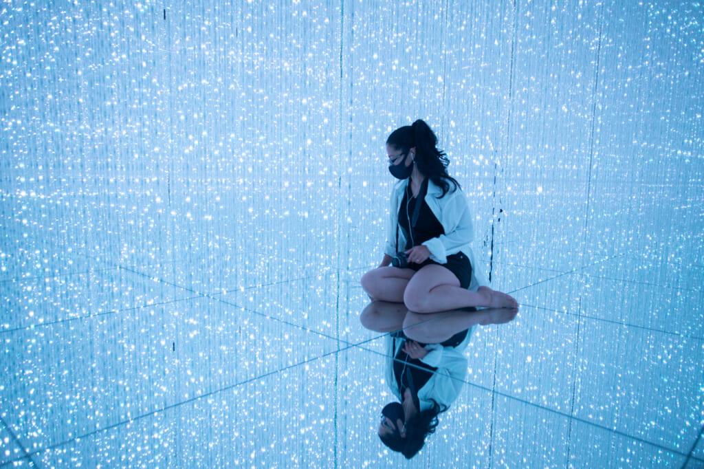 une personne et son reflet dans une exposition de teamLab Planets