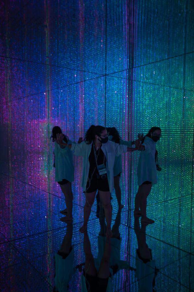 une personne entourrée de ses reflets dans une exposition de teamLab Planets