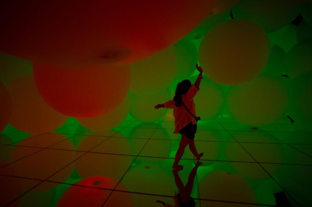 sphères roucges et vertes dans une exposition de teamLab