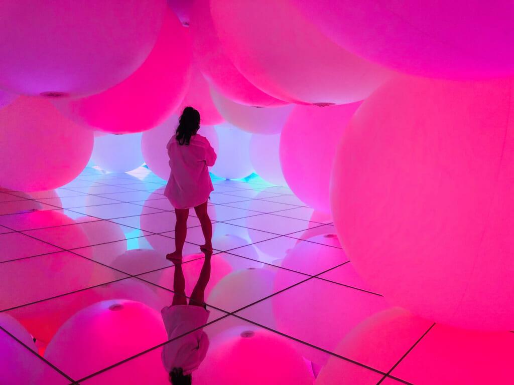 Sphères roses lumineuses au dessus d'un sol recouvert de miroirs