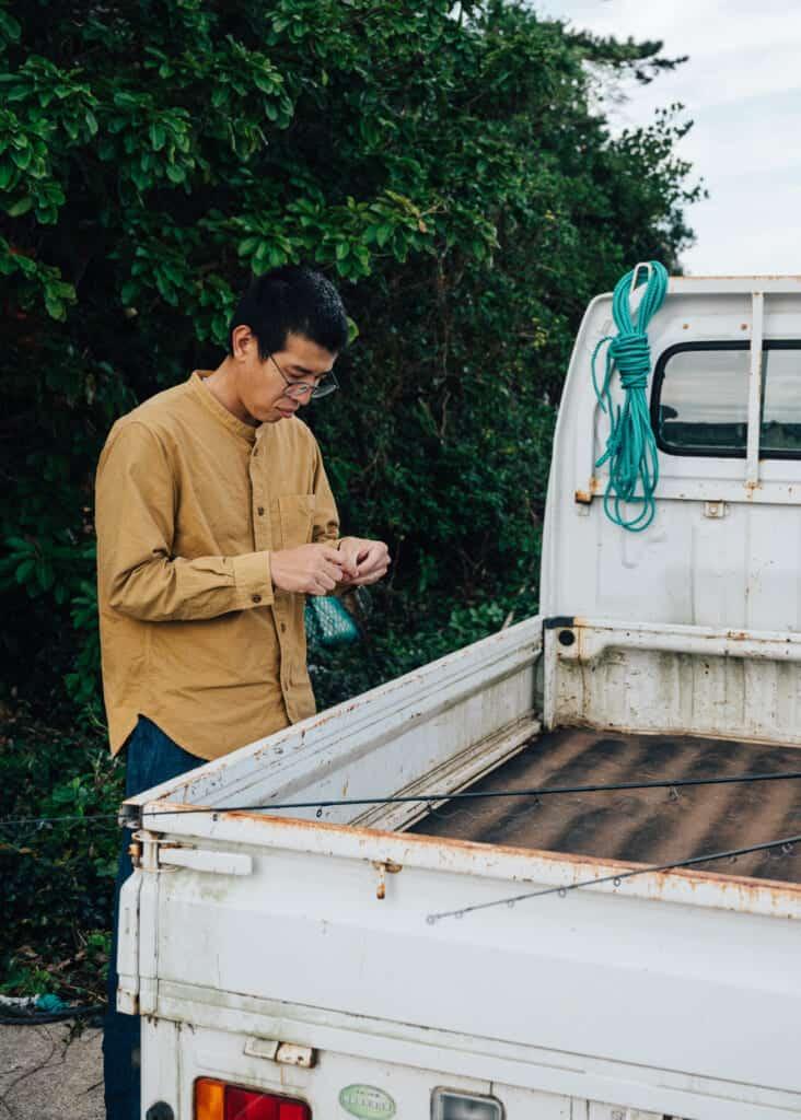 Hashi, de Yanoya, prépare la ligne de sa canne à pêche