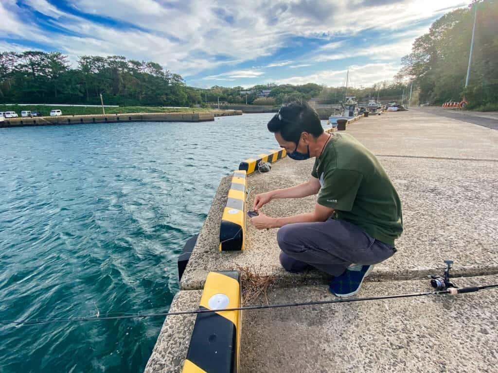 Todd prépare la ligne de sa canne à pêche à Ojika