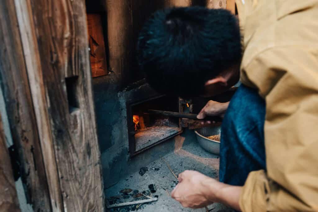 Allumer le feu sous la baignoire de chambres d'hôtes traditionnelles à Ojika