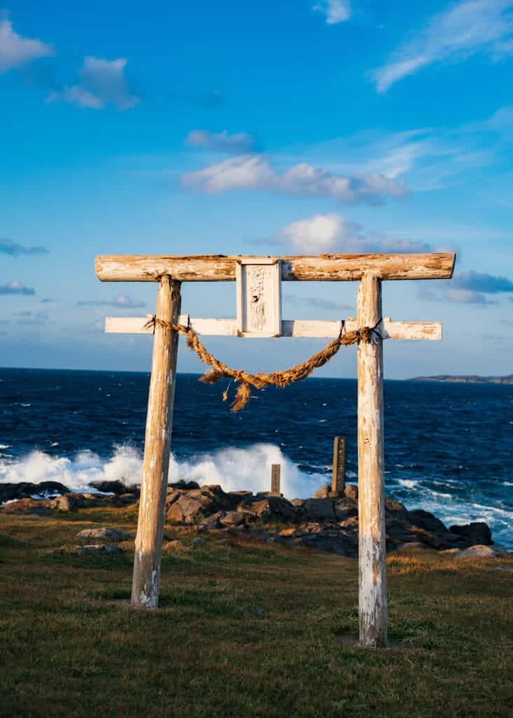 vieux torii blanc en bord de mer au Japon