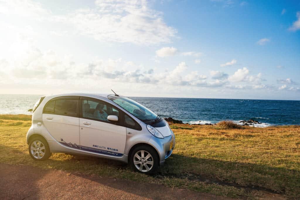 Une voiture électrique garée près des côtes des îles de Goto