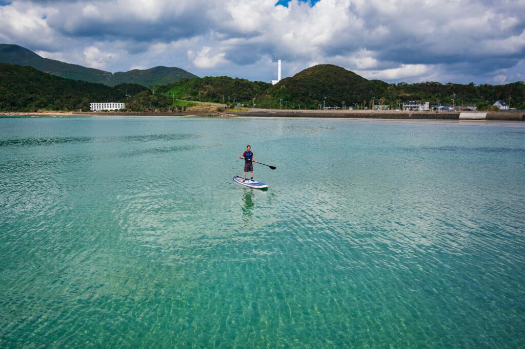un homme faisant du stand up paddle sur des eaux calmes