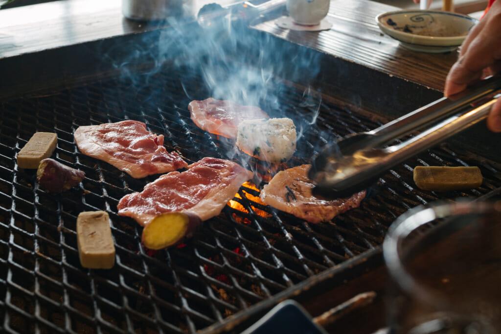 des tranches de porc entrain de cuire sur un barbecue japonais
