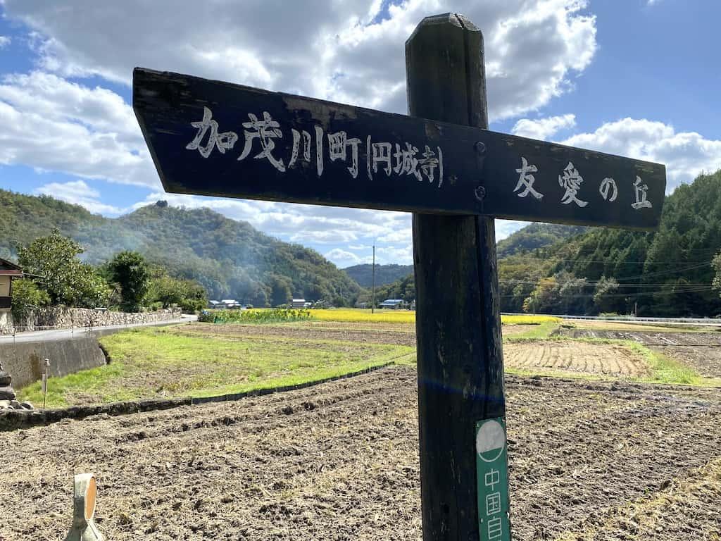 Un panneau indique Kamogawacho devant des champs d'agriculture à Okayama